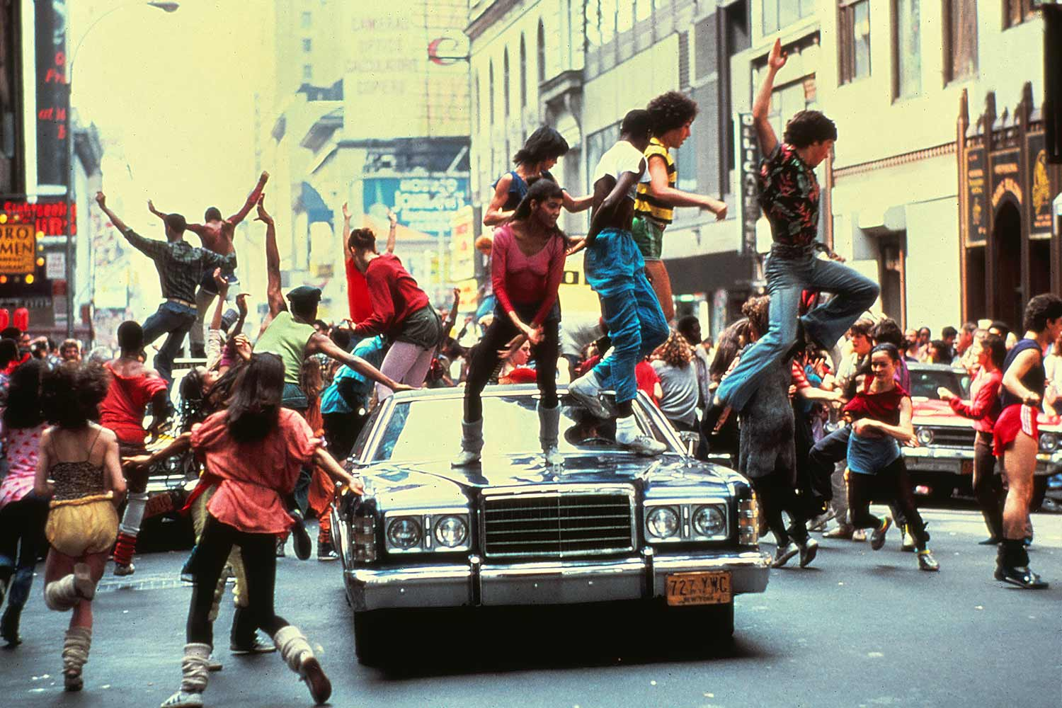 Still from the movie Fame showing people dancing on a car in New York City.