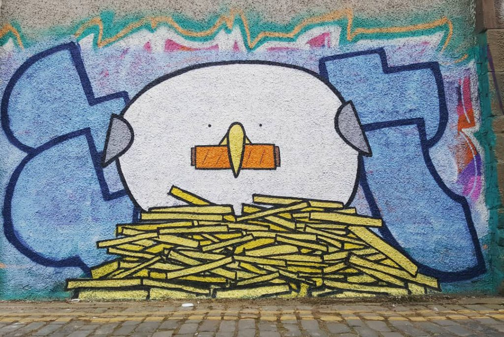 Grafitti of a seagull protecting a pile of fries