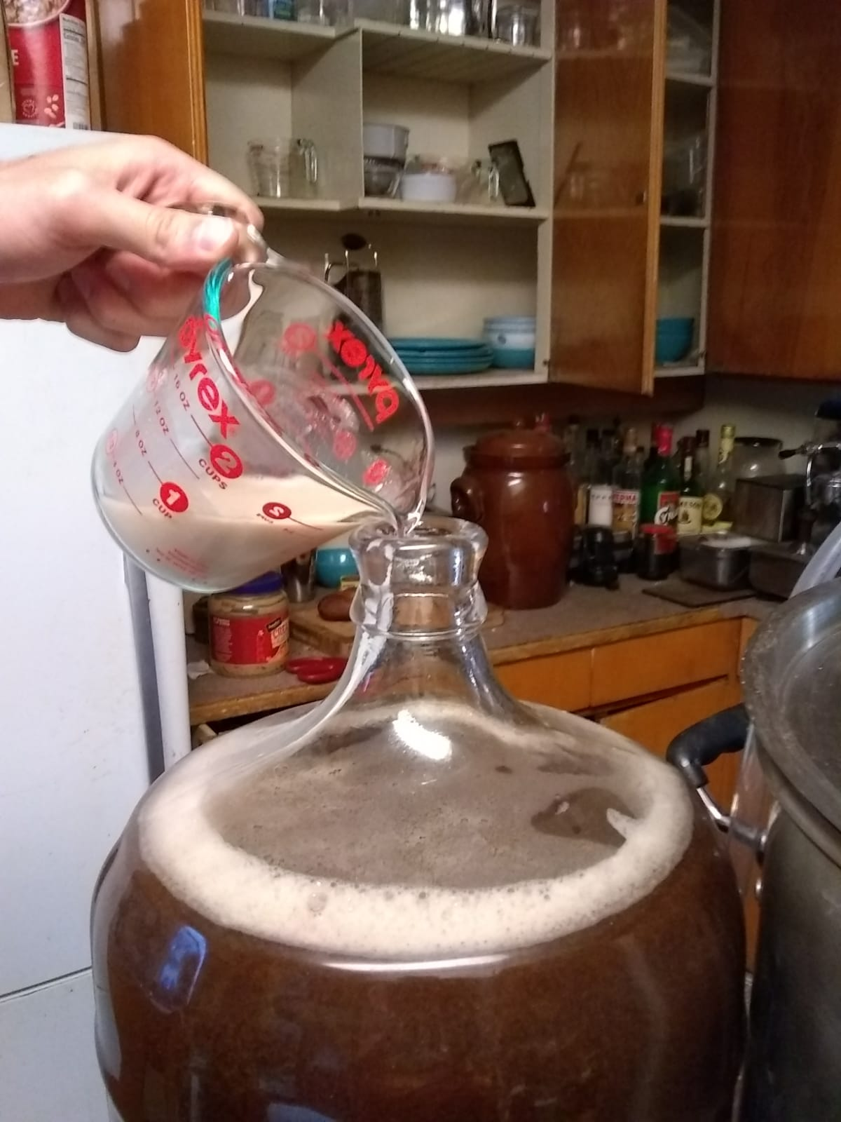 A hand pouring a measuring cup with yeast into the fermentator.