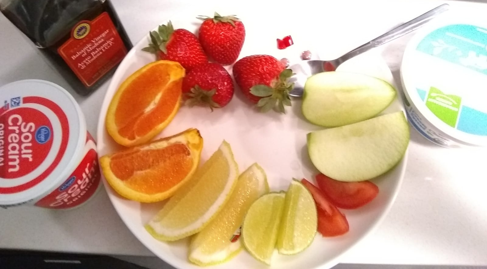 Sour foods: balsamic vinegar, sour cream, strawberries, orange slices, lemon slices, lime slices, tomato slices, granny smith apples, chili pepper and cream cheese.