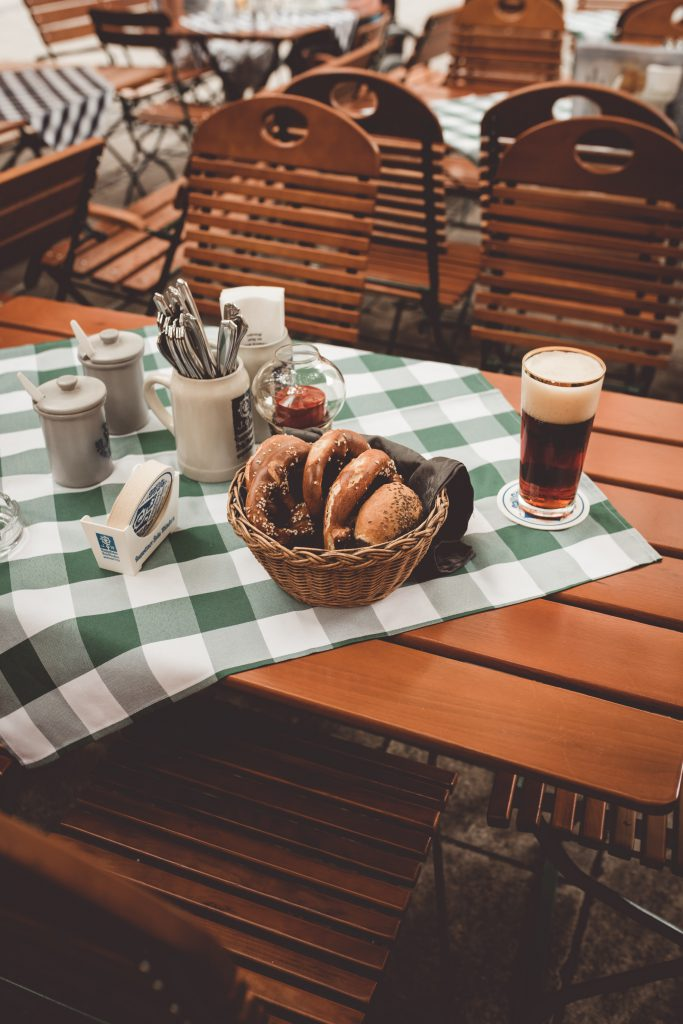 A table with beer and a basket of pretzels.