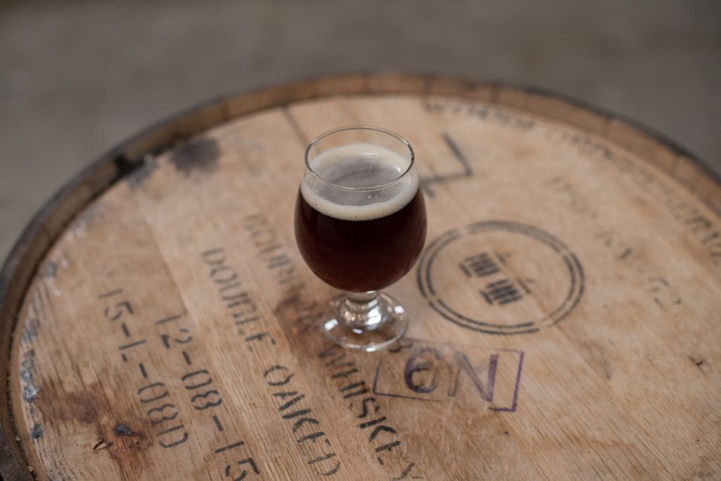 A red/brown glass of beer on a wooden barrel.