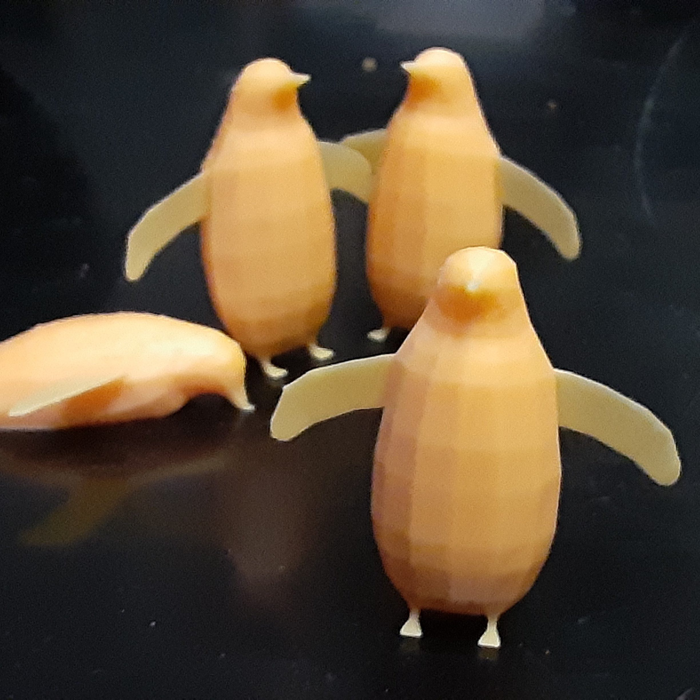 4 penguins 3D printed in orange resin. 3 are standing upright with wings spread out, one is on its belly.