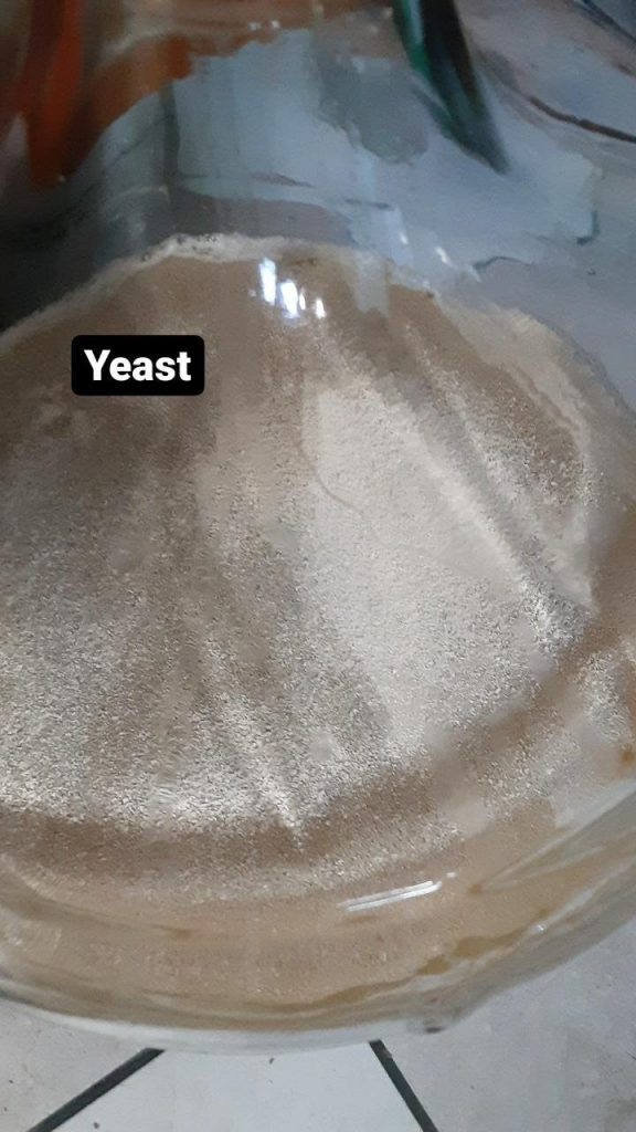 Picture of dry yeast floating on the liquid surface.